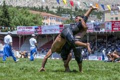 Un luchador levanta a su opositor hacia el cielo durante la competencia en el festival de lucha del aceite turco de Elmali en Elm Fotos de archivo