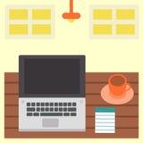 Un lugar de trabajo con el ordenador portátil, la taza y la libreta Imágenes de archivo libres de regalías