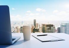 Un lugar de trabajo en una oficina panorámica moderna en Manhattan, New York City Un ordenador portátil, la libreta y una taza de imagen de archivo libre de regalías