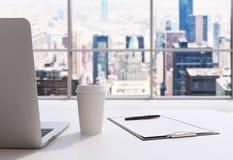 Un lugar de trabajo en una oficina panorámica moderna en Manhattan, New York City Un ordenador portátil, la libreta y una taza de Fotos de archivo