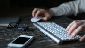 Un lugar de trabajo moderno Trabajo nocturno Un hombre se sienta en un ordenador y los tipos en el teclado almacen de video