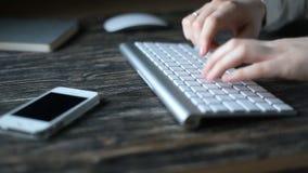 Un lugar de trabajo moderno Trabajo nocturno Un hombre se sienta en un ordenador y los tipos en el teclado almacen de metraje de vídeo