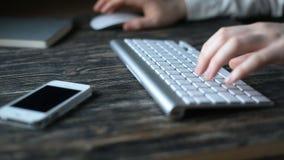 Un lugar de trabajo moderno Trabajo nocturno Un hombre se sienta en un ordenador y los tipos en el teclado metrajes