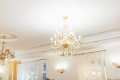 Un lustre en cristal allumé sous le plafond blanc Images stock