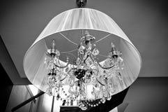Un lustre en cristal avec une nuance blanche Photos stock