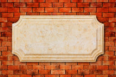 Un mármol del letrero en la pared de ladrillo Foto de archivo libre de regalías
