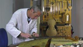 Un más luthier substituye el tacto de un violoncelo metrajes