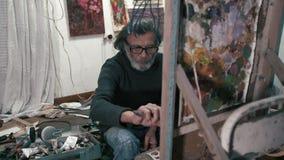 Un más viejo artista barbudo dibuja una imagen con un cuchillo 4K almacen de metraje de vídeo