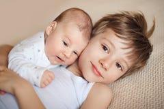 Un más viejo hermano que abraza al bebé recién nacido Foto de archivo