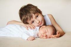 Un más viejo hermano que abraza al bebé recién nacido Imagen de archivo libre de regalías