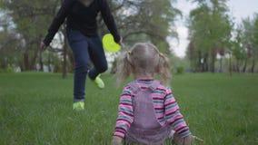 Un más viejo hermano y pequeño funcionamiento de la hermana en parque verde hermoso La pequeña muchacha se cae abajo y el muchach almacen de metraje de vídeo