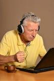 Un más viejo hombre con el ordenador portátil Foto de archivo