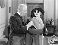 Un más viejo hombre que ayuda a una mujer joven en su capa (todas las personas representadas no son vivas más largo y ningún esta Fotografía de archivo libre de regalías
