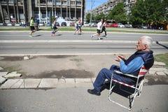 Un más viejo hombre se está sentando en una silla y está dando la ayuda a los corredores Imagen de archivo