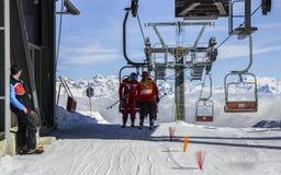 Un más viejo hombre y el adolescente consiguen de la telesilla en la estación de esquí con las montañas italianas majestuosas en  Imagen de archivo