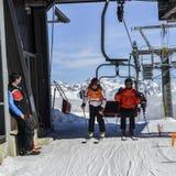 Un más viejo hombre y el adolescente consiguen de la telesilla en la estación de esquí con las montañas italianas majestuosas en  Foto de archivo libre de regalías
