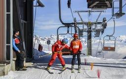 Un más viejo hombre y el adolescente consiguen de la telesilla en la estación de esquí con las montañas italianas majestuosas en  Fotografía de archivo libre de regalías