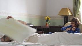 Un más viejo sueño del hermano en cama y el pequeño hermano lo despiertan mientras que toca el violín Almohada de tiro del indivi almacen de metraje de vídeo