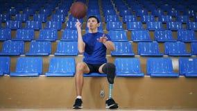 Un mâle avec une jambe artificielle joue avec une boule de panier tout en se reposant banque de vidéos