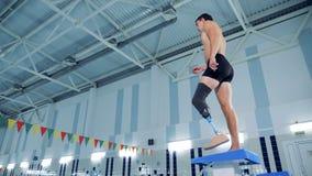 Un mâle avec une jambe prosthétique dispose à nager dans une piscine clips vidéos