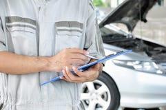 Un mécanicien tenant le presse-papiers devant le moteur de voiture Image libre de droits