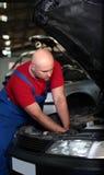 Un mécanicien travaillant à un véhicule Image libre de droits