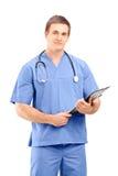 Un médico de sexo masculino en un uniforme que presenta con el tablero en el suyo Imagen de archivo