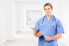 Un médico de sexo masculino en un uniforme que sostiene un tablero y un posin Foto de archivo libre de regalías