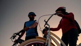 Un ménage marié sur des bicyclettes à l'arrière-plan du Soleil Levant va sur un tour de vélo clips vidéos