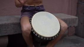 Un músico de la calle juega el tambor Hippies carismáticos en el centro de la ciudad El batería juega adornos africanos metrajes