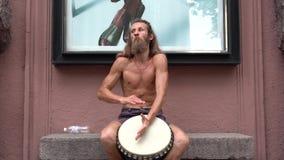 Un músico de la calle juega el tambor Hippies carismáticos en el centro de la ciudad El batería juega adornos africanos almacen de video