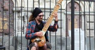 Un músico de la calle se sienta en la acera y juega el sitar del instrumento almacen de metraje de vídeo