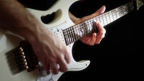 Un músico juega en una guitarra eléctrica blanca en un fondo negro El hombre está jugando la roca almacen de video