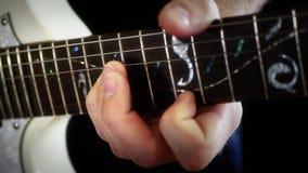Un músico juega a solas en una guitarra eléctrica blanca en un fondo negro, primer El hombre está jugando la roca metrajes