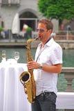 Un músico que toca el saxofón en la calle al lado del río de Reuss en Alfalfa