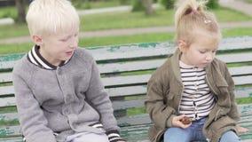 Un m?s viejo hermano abraza suavemente a una hermana m?s joven en el parque almacen de video