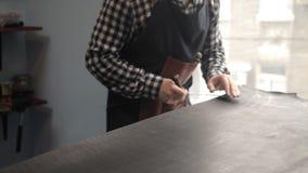 Un maître d'un gouvernail de direction en cuir coupe des billettes pour faire une ceinture Procédure pour la fabrication des cein banque de vidéos