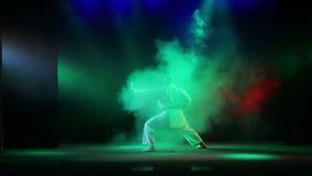 Un maître de karaté dans un kimano blanc avec une ceinture noire sur un fond noir avec de la fumée colorée est engagé dans le kar banque de vidéos