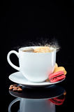Un macaron éclabousse une tasse de café sur la surface en verre photo stock