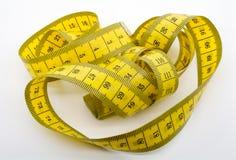 Un macro colpo di un nastro di misurazione giallo Immagine Stock