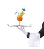 Un maggiordomo che tiene un cassetto con il cocktail su esso immagine stock libera da diritti