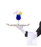 Un maggiordomo che tiene un cassetto d'argento con il cocktail su esso immagine stock