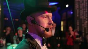 Un mago atractivo en un sombrero negro habla con la audiencia almacen de metraje de vídeo