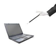 Un mago que sostiene una varita mágica sobre una computadora portátil Fotografía de archivo libre de regalías