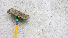 Un magro sucio amarillo de la multitud o de la esponja en el muro de cemento sucio La fregona del piso se utiliza para limpiar el Foto de archivo