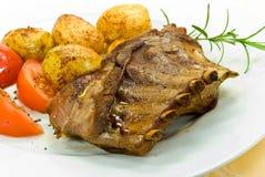 Un maiale di lattante arrostito con le patate e l'insalata Immagini Stock