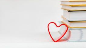 Un maigre de forme de coeur sur la pile de livres placée sur la surface blanche Photographie stock libre de droits