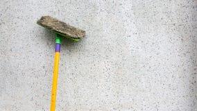 Un maigre sale jaune de foule ou d'écouvillon sur le mur en béton sale Le balai de plancher est utilisé pour nettoyer le plancher photographie stock libre de droits