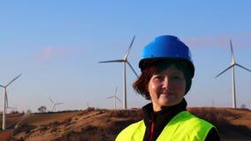Un main-d'œuvre féminine sur un fond des turbines de vent banque de vidéos