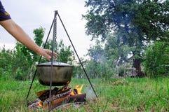 Un man& x27; la mano de s enciende un fuego debajo de una cacerola, que se coloca en un fuego imagenes de archivo